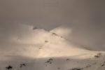 Creuament de muntanyes entre núvols al capvespre